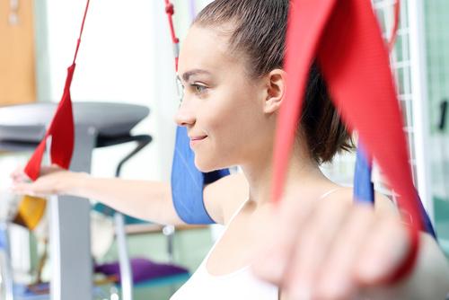 Rehabilitacja kończyn górnych. Kobieta ćwiczy ręce na podwieszkach.