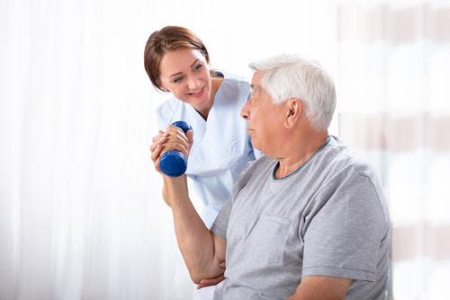 Pielęgniarka pomaga starszemu mężczyźnie w ćwiczeniach
