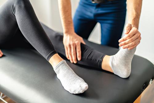 Rehabilitacja. Mężczyzna trzyma stopę kobiety w czasie rehabilitacji