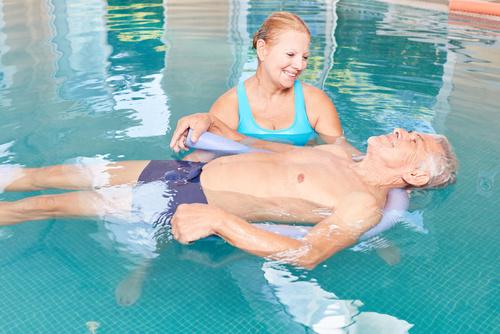 Senior uczy się relaksować z jogą wodną