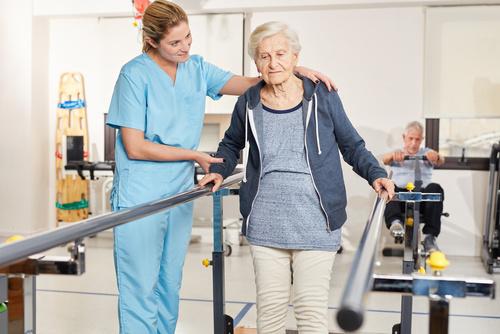 Terapeuta wspiera starszą kobietę na bieżni