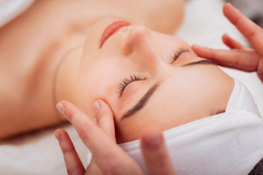 Piękna kobieta zamyka oczy, czując się całkowicie zrelaksowana w czasie masażu