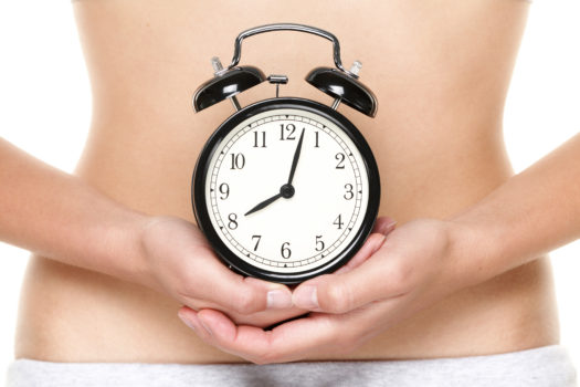 Kobieta trzyma zegar przed brzuchem.